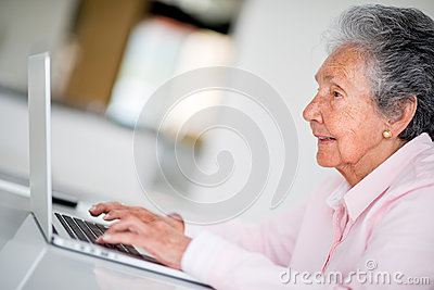 elder-woman-using-computer-looking-very-happy-31030272